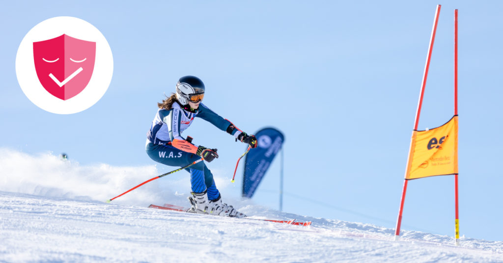 Young female ski racer competing in ISSC, covid guarantee badge